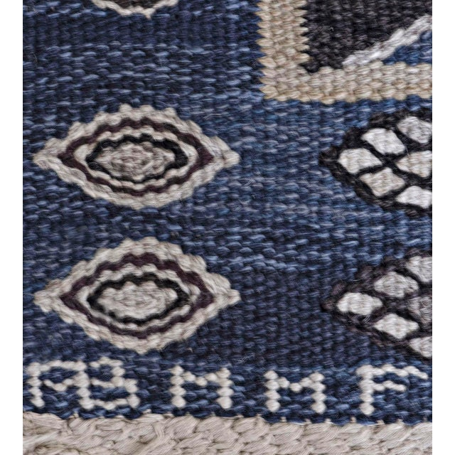 This signed mid-century Swedish rug has a shaded blue field with three central columns of linked chocolate-brown and soft-...