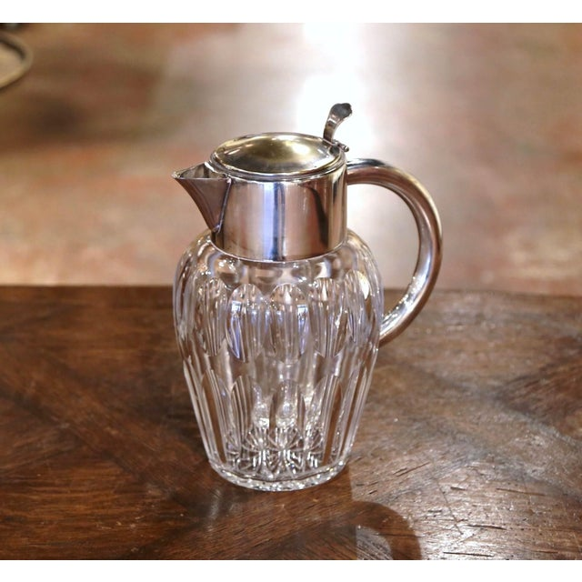 Crafted in France circa 1950, the large pitcher features a round cut glass body and dressed with a silvered brass neck,...