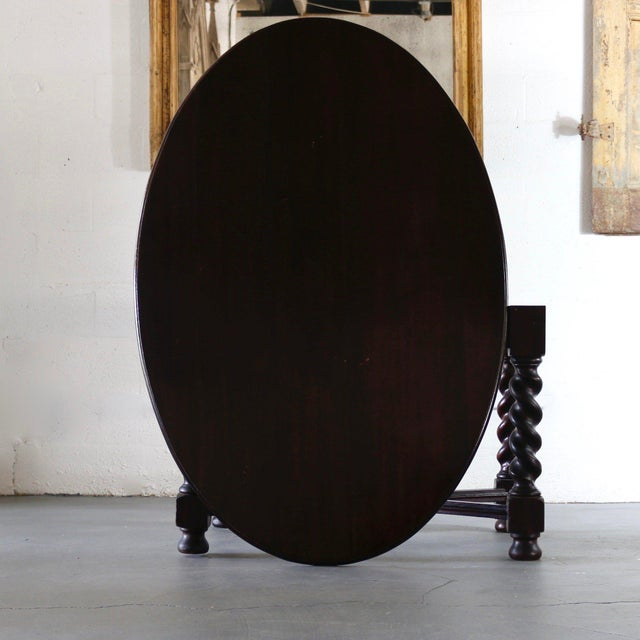 19th Century Spanish oval turned leg table. A dark finish and coral legs add a masculane stance and feminine flare.