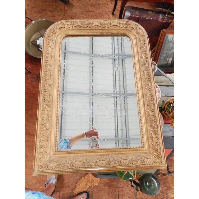 """Muted gold patina adorns this antique mirror. Made in France circa 1900. 12 lbs. 22"""" X 30 1/2"""" frame 14 1/2 X 22 1/2""""..."""
