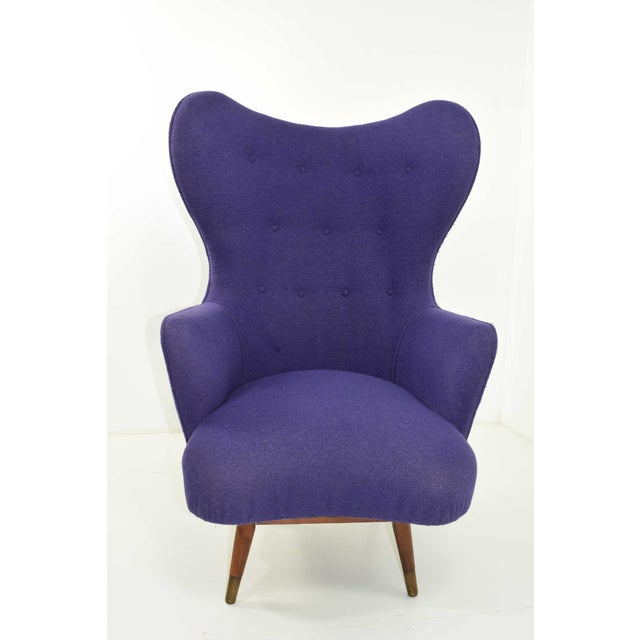 A very unique Danish lounge chair shaped somewhat like the egg chair by Arne Jacobsen. Has a solid teak base, brass...