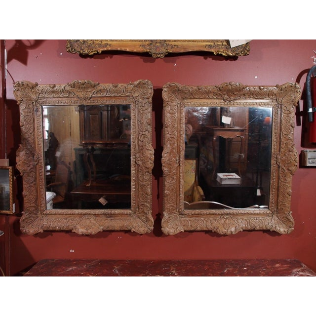 Pair of 19th century French carved oak mirrors. Glass is new. Frames are solid carved wood, Regence style with shell...