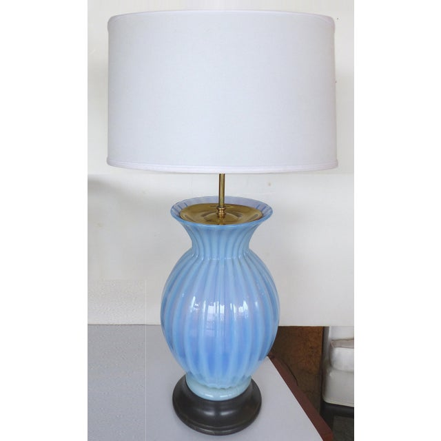 A large mid-century Murano glass table lamp by Marbro Lamp Co. supported by an ebonized wood base with brass fittings. The...