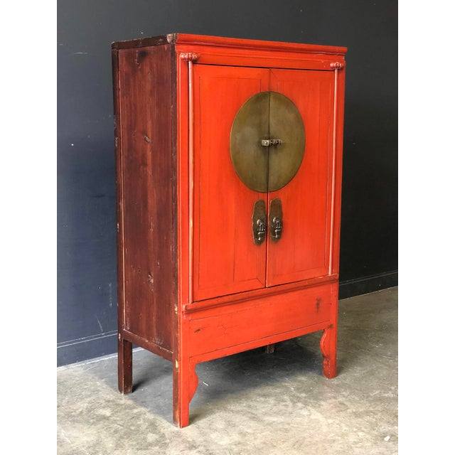 A stunning antique Asian cabinet dating from the early 1900's. Original heavy brass hardware makes a statement against a...