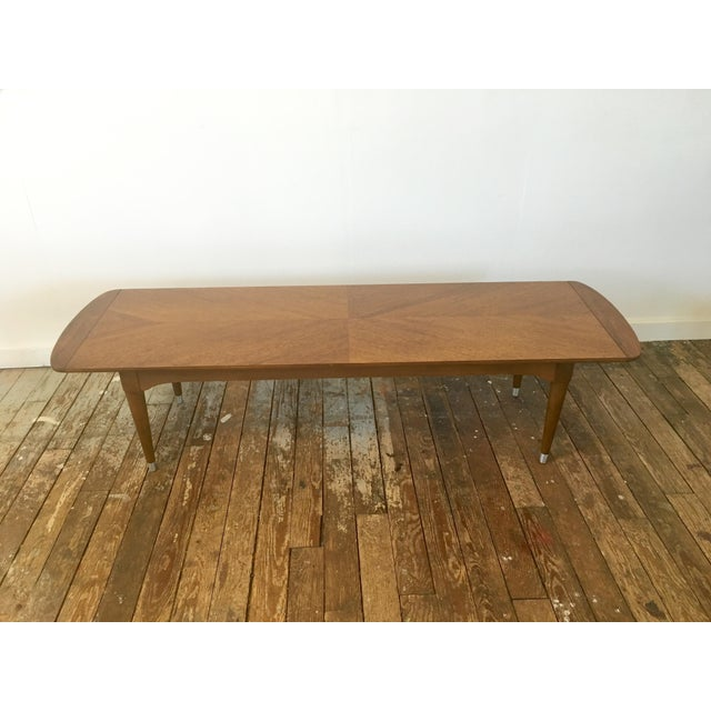 A simple walnut coffee table with interesting wood grain. The table is made from walnut and sits on pencil legs with...