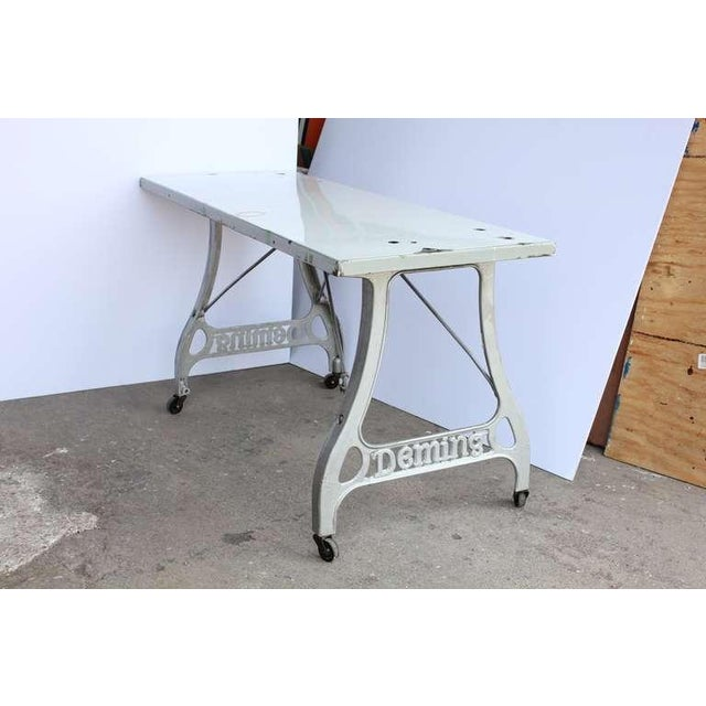 Antique industrial table with original porcelain top and cast iron base.