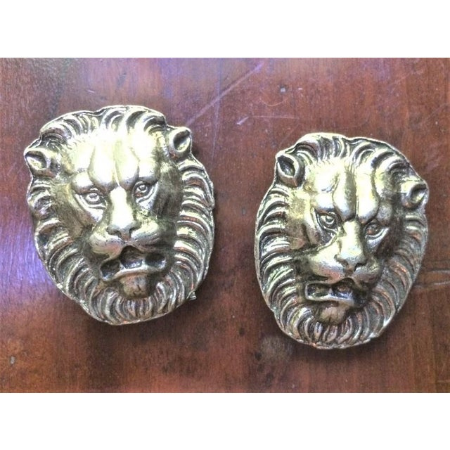 A pair of vintage metal lions heads made and purchased in Rome and styled after ancient Roman design. These are ornamental...