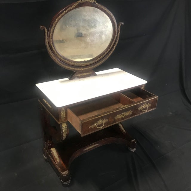 A French Charles X Empire period mahogany dressing table with original marble top and gorgeous bronze decoration. Some...