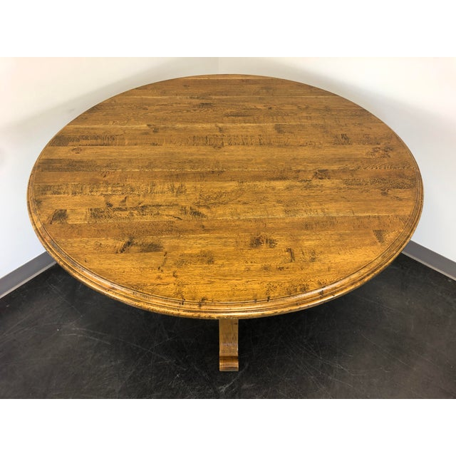 """A 52"""" round dining table by Palacek. Solid hardwood with a distressed finish. Pedestal base. 52w 52d 30.5h Excellent..."""