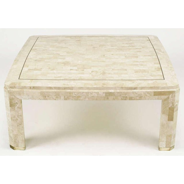 Tessellated fossil coffee table with a stepped and beveled edge top with inlaid brass border. Sculpted top is slightly...
