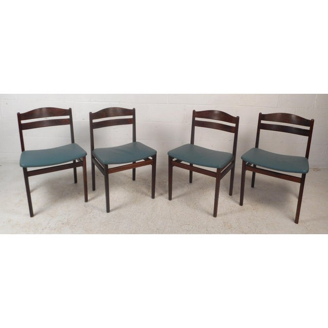 This stunning set of four vintage modern dining chairs feature a rosewood frame with leather seats. Sleek design with a...