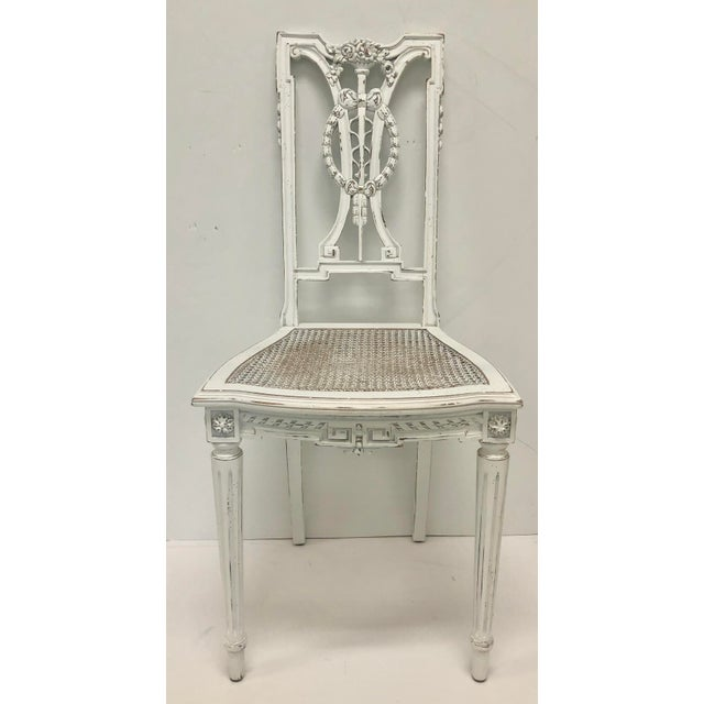 F. Louis XVI style chair with hand carved wooden elements and caned seats. Painted white with sanded wood accents on the...