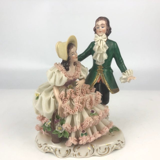 This vintage porcelain figurine features German Dresden style including porcelain lace skirt and delicate handpainted...