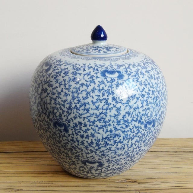 A ceramic painted blue and white jar with a lid and a filigree motif throughout.
