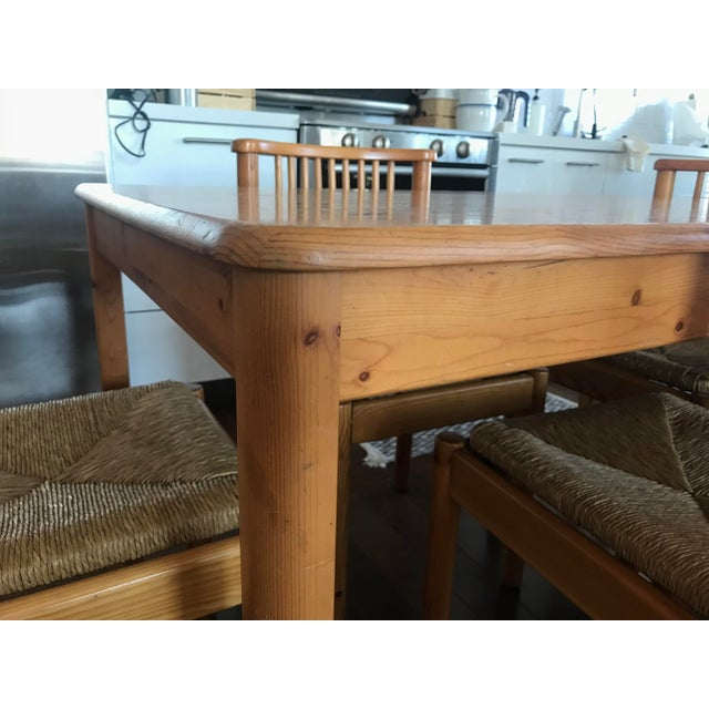 Set of four solid pine and rush spindle back chairs and dining table. This is the perfect mid-century small dining set. In...