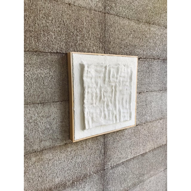 This sculptural plaster painting creates a network of light and shadow through a three dimensional grid of right angles....