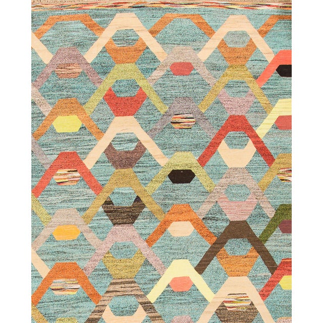 Beautiful hand-knotted modern Kilim rug with a turquoises field, and multi color accents an allover abstract design. This...