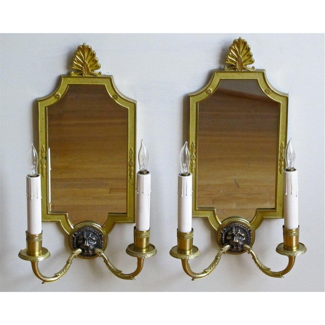 Pair of French two-light mirrored finely detailed brass wall sconces with lion motif in contrasting bronze finish. Newly...
