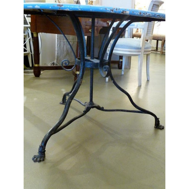 A wonderful blue and black cast iron cafe table with original paint. Iron paw feet.