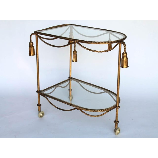Gilded rope & tassel 2-tier bar cart with removable glass shelves and casters. No makers mark. Some wear to gilded finish,...
