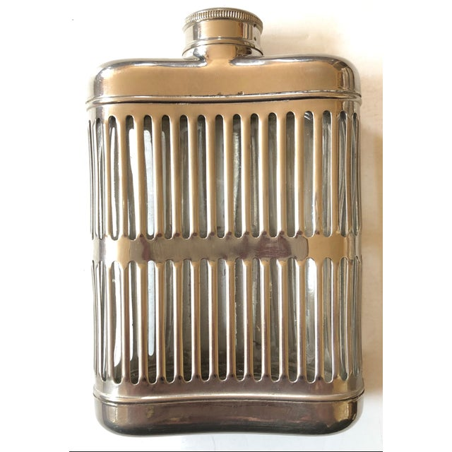 Curved to fit comfortably, this hip flask is designed with a silver metal cage and glass interior. Screw on top is fitted...