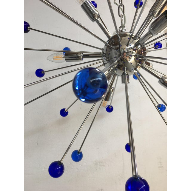 Flush-mount or Wall sconce with a chrome base and round Murano glass in a dark blue color. The fixture is in the classic...