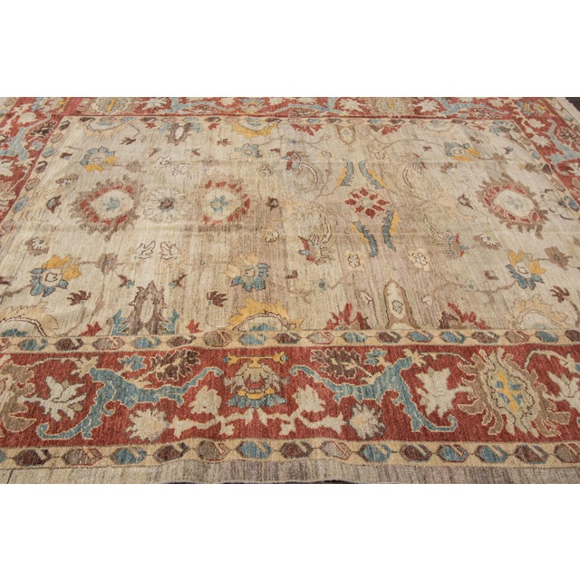 A hand-knotted artisan Sultanabad rug with a geometric pattern on a beige field. Accents of red, blue, brown and beige...