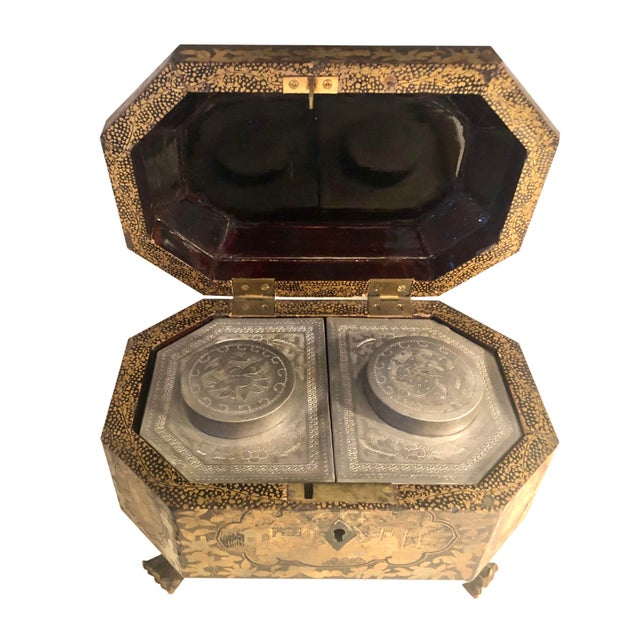 A 19th century Chinese chinoiserie tea box with dragon feet and a complete pewter interior