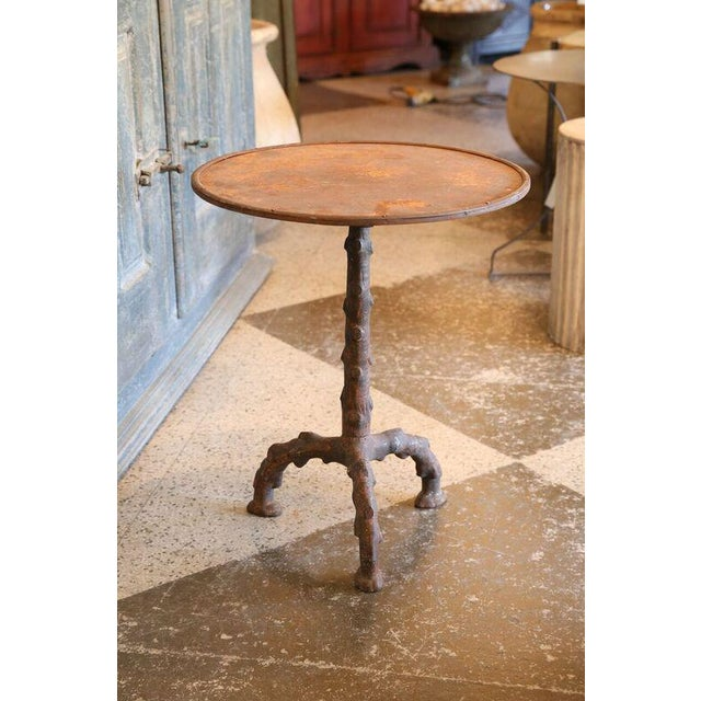 French guéridon table, circa 1950, with cast-iron faux bois base, retaining traces of its original painted finish, and a...