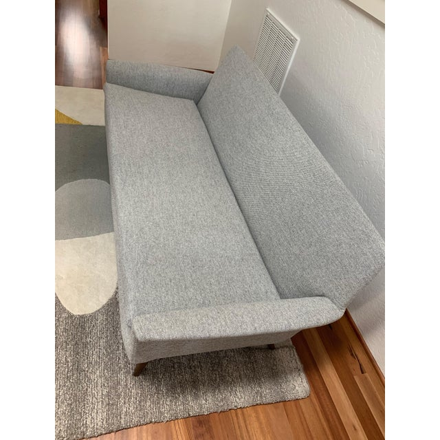 Classic, elegant mid century modern sofa in excellent shape with brand new upholstery. Fabric is a light grey Maharam...