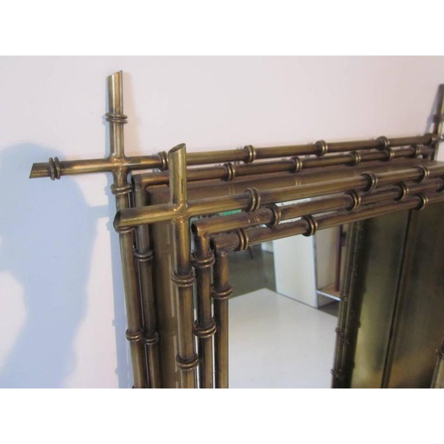 A Jere gold gilt faux bamboo styled wall mirror with shadow boxed frame layered with metal bamboo rods and signed to the...