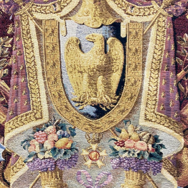 A large and sumptuous tapestry showing a Coat of Arms with a golden eagle centered in a shield above two cornucopia filled...