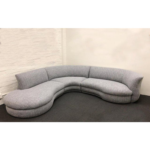 A glamorous 1990s three-piece sectional sofa. The sectional has been newly recovered in a light gray with black tones...