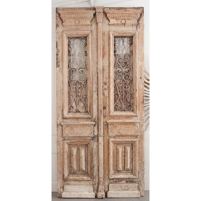 This tall and imposing pair of Napoleon III-style painted-pine and wrought-iron entry doors are from France, c. 1900's,...