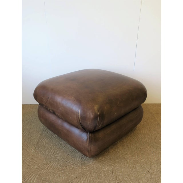 A Postmodern or Modern style brown leather ottoman by George Smith, England, circa 1990s. Ottoman is professionally...