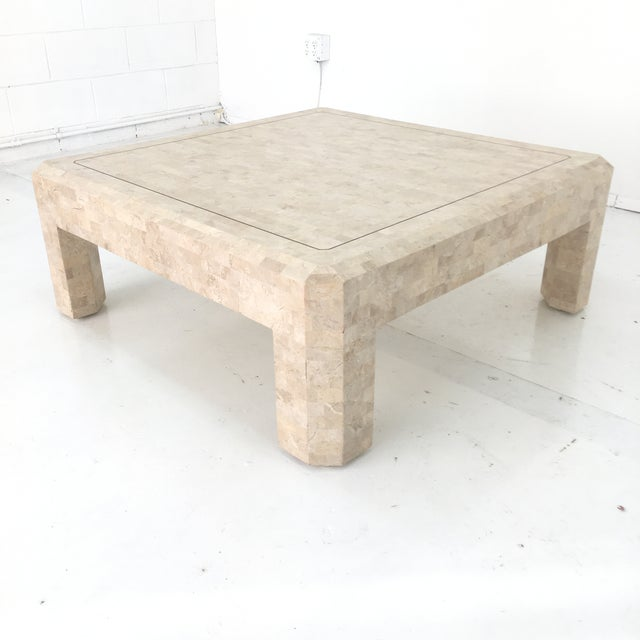 Well persevered stone coffee table with a strong stable design. This item features interesting thing lining of brass...