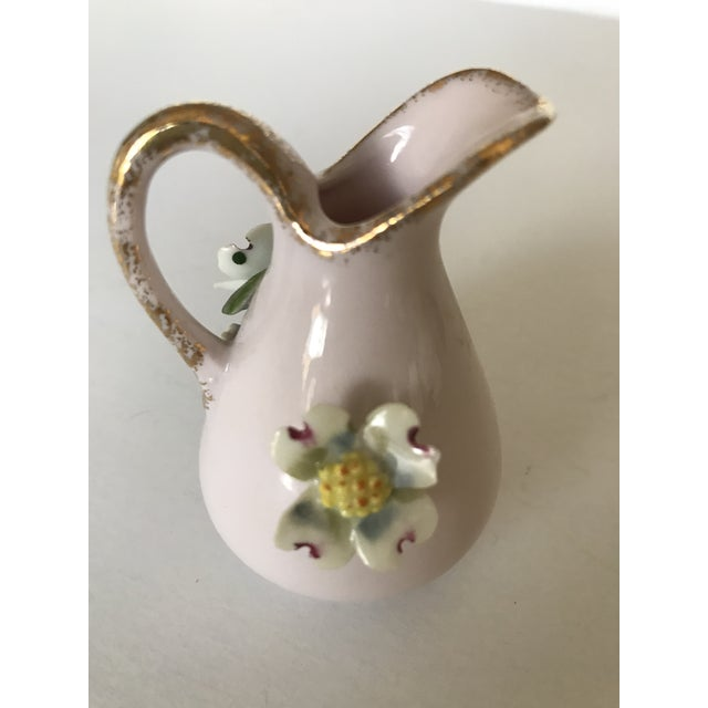 Absolutely beautiful little pitcher with raised porcelain dogwood flowers. Soft pink china with a gold rim. This is scaled...