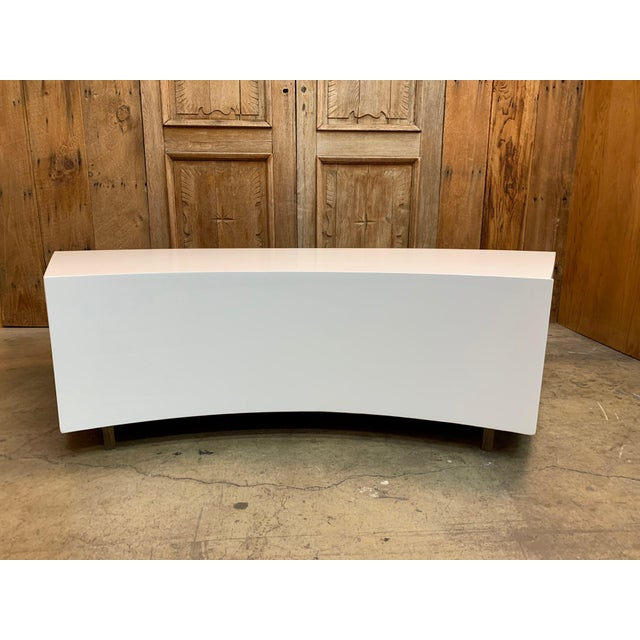 White satin lacquer over wood atop lucite support bars with curved front drawer. Perfect for curved sofa.
