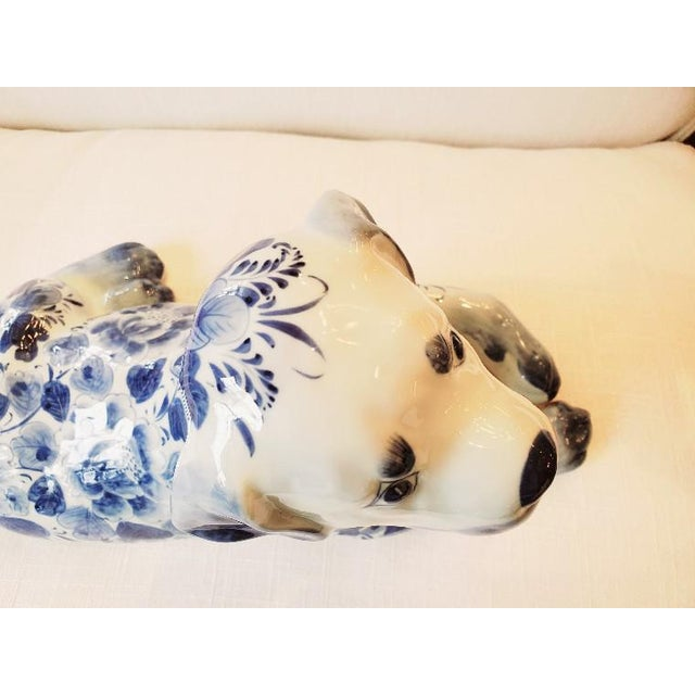 An adorable reclining porcelain dog accessory to dress up any book shelf or table in a pretty blue and white pattern.