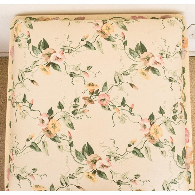 An ivory painted vanity stool with a padded seat that is upholstered in a floral motif printed textile. The pattern in the...