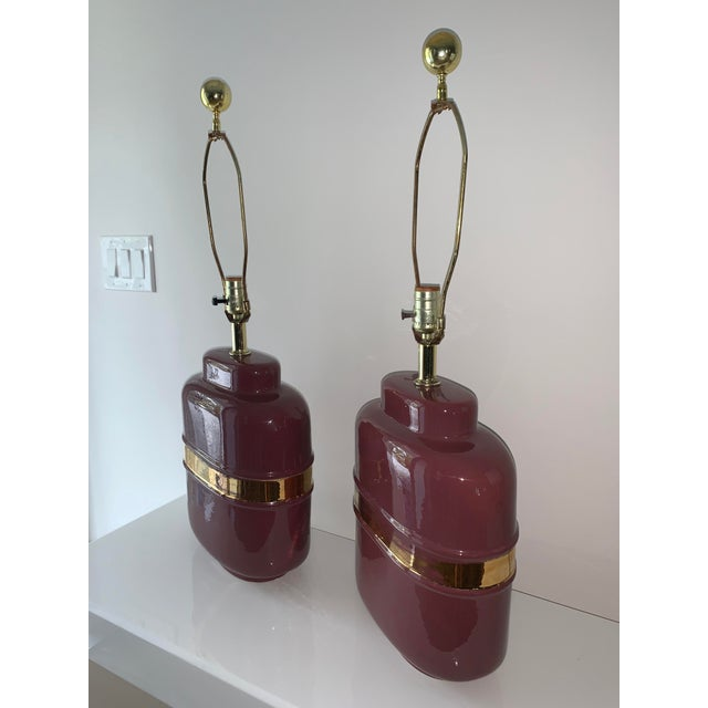 Super cool pair of mauve and gold lamps with abstract form. Ceramic body with a metallic horizontal gold line around the...