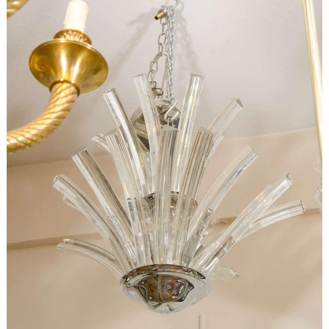A 20th century two-tier Murano chandelier with tri-pointed curved glass rods. This chandelier takes nine candelabra base...
