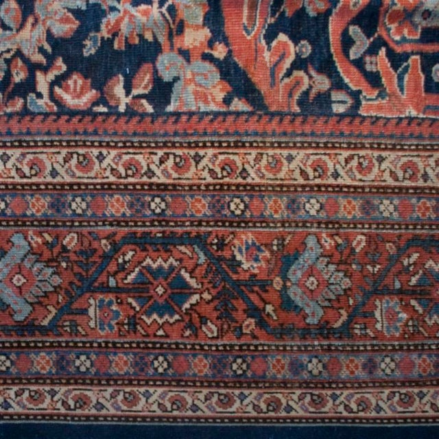 A 19th century Persian Sultanabad carpet with all-over floral and vine pattern on an indigo background, surrounded by a...