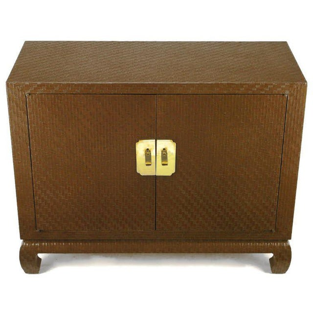 Chocolate brown lacquered grass cloth cabinet from Baker's Far East Collection. Ming style turned legs, and large brass...