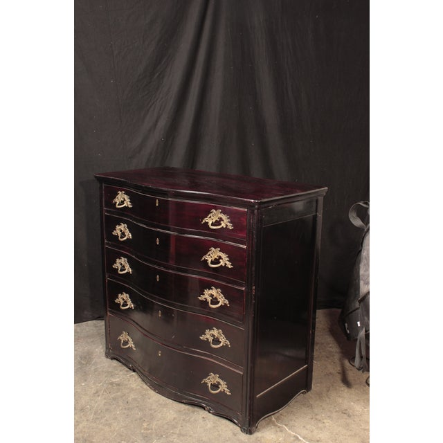 A mid-19th century continental serpentine chest of drawers. Ebonized in oxblood with lamp black overtones, this five...