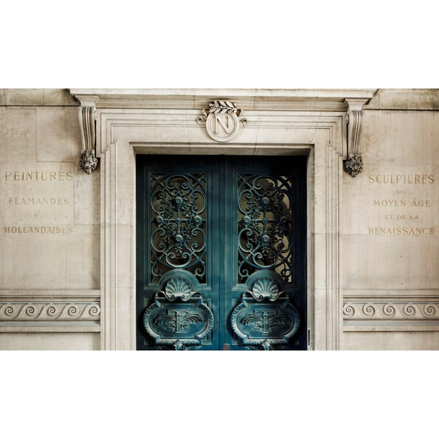 One of many entrance doors to the Louvre Museum in Paris, France. Napoleon's emblem sits proudly above the doors. This...