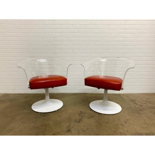 Pair of vintage midcentury Space Age acrylic swivel chairs with blood orange leather and newly powder coated bases.