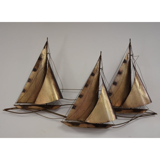 A Curtis Jere signed in two places brass sculpted sailboats with wrapped brass sails and some oxidation.