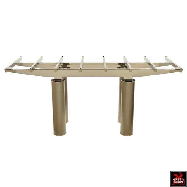 This elegant dining table has a impressive structural design in chrome, that rest on four large pillar legs in brushed...