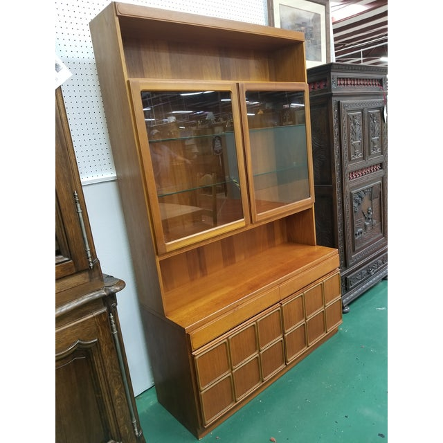 Mid century modern china cabinet by McIntosh Furniture. This cabinet comes it two pieces and it features a top shelf over...